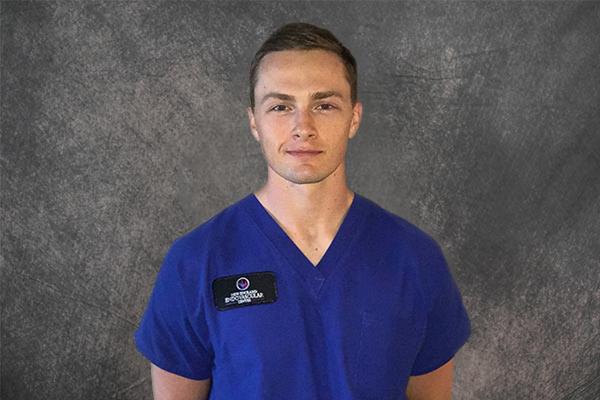 male nurse wearing blue scrubs against a gray background