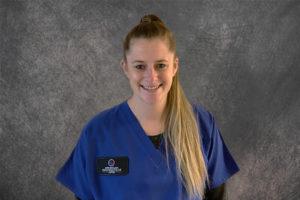 nurse wearing blue scrubs against a gray backdrop